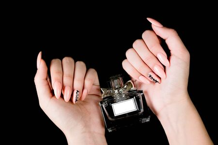 Manicured girl hands and perfume bottle on a black background