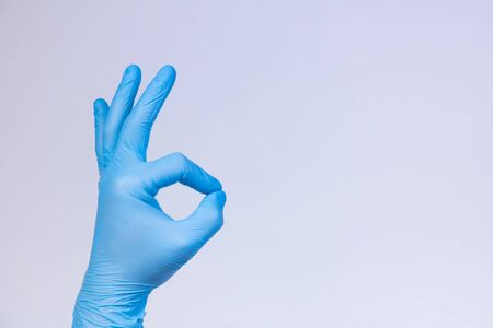 Ok sign is showed by left man hand in a blue medical glove on a white background. Okay. All right