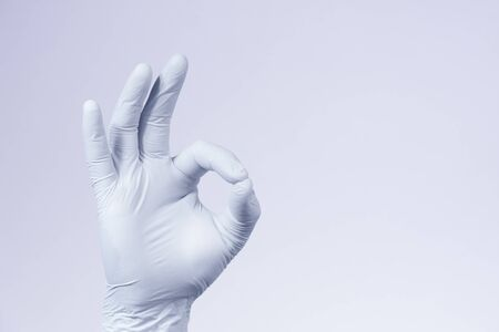 Ok sign is showed by right man hand in a white medical glove on a white background. Okay. All right Reklamní fotografie