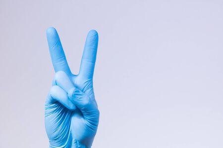 V sign is showed by right man hand in a blue medical glove on a white background. The symbol of Victory. Victory over a virus.