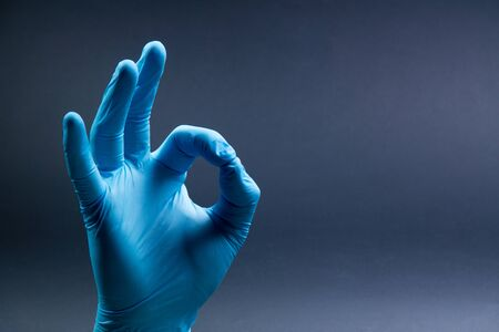 Ok sign is showed by right man hand in a blue medical glove on a black background. Okay. All right