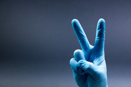 V sign is showed by right man hand in a blue medical glove on a black background. The symbol of Victory. Victory over a virus.