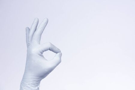 Ok sign is showed by left man hand in a white medical glove on a white background. Okay. All right