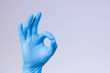 Ok sign is showed by right man hand in a blue medical glove on a white background. Okay. All right