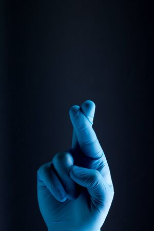 Sign for hope is showed by right man hand in a blue medical glove on a black background. The good luck symbol.