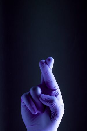 Sign for hope is showed by right man hand in a purple medical glove on a black background. The good luck symbol. Reklamní fotografie