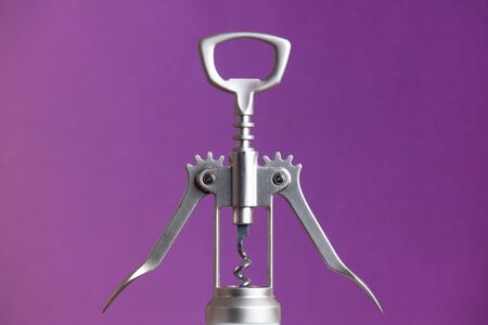 Metallic corkscrew with two levers like humanoid robot spreads it's arms on a purple background.