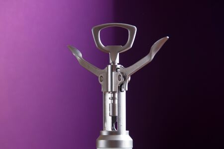 Metallic corkscrew with two levers like humanoid robot spreads it's arms wide on a gradient purple background.