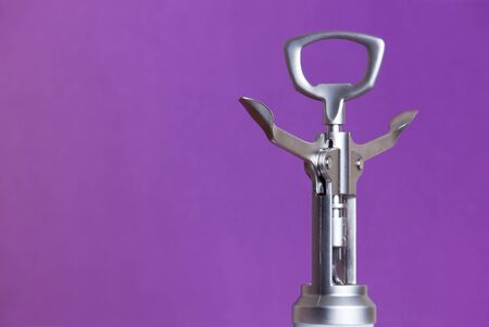 Metallic corkscrew with two levers like humanoid robot spreads it's arms wide on a purple background.