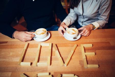 bebes lindos: pareja manos de café en una mesa de madera. inscripción amor en la mesa