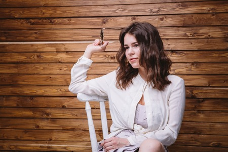 a young girl with long hair, white clothing, sunglasses in hand sitting on a chair and wooden background Stock Photo