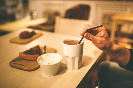 gingerbread man: cocoa with marshmallows and cake on the table. Hand mixed drink. Wooden table, metal spoon Stock Photo