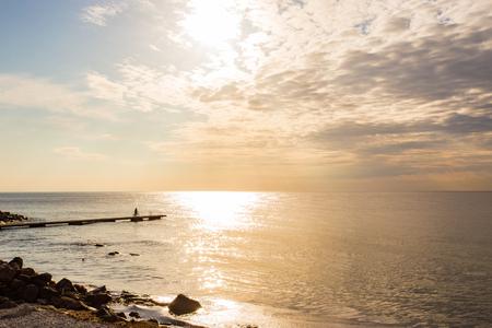 海に、桟橋、遠くにシルエット上のサイクリスト。北欧、スウェーデン