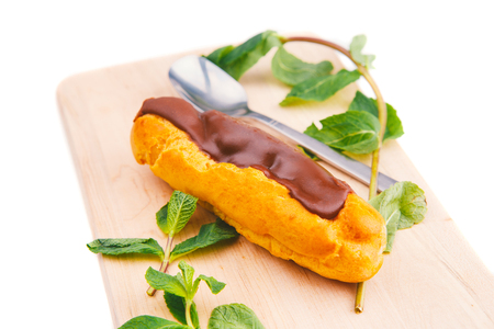 custard cake, Eclair with chocolate and cream dessert on a wooden plate, white background, mint Stock Photo