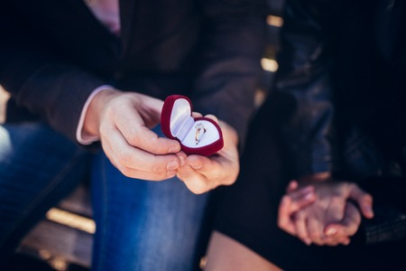 suitor: Proposal. Mans hands are holding a red gift box in the form of red heart with a ring. Stock Photo
