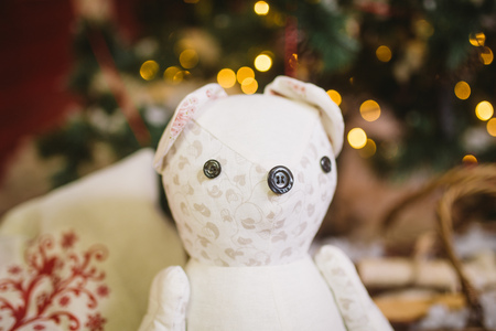 Teddy bear gift sitting under decorated with lights Christmas tree with gift boxes Foto de archivo