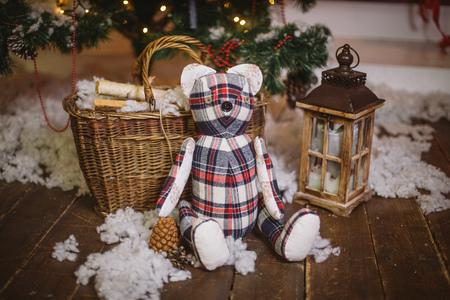 Regalo del oso de peluche sentado bajo decorado con luces Árbol de Navidad con cajas de regalo Foto de archivo