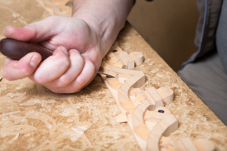 Artisan woodcarver creates a furniture ornament. Woodcarvers hands, chisels, tools, wood-carved ornament.