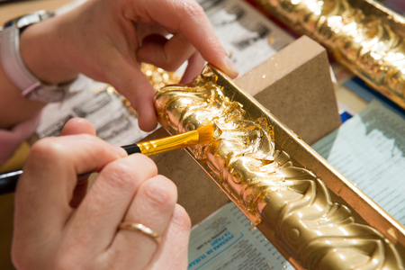 female hand painting with a brush baguette for ceiling and walls in gold color Stock Photo