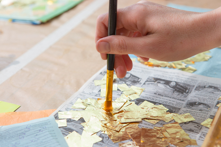 woodcraft: female hand painting with a brush baguette for ceiling and walls in gold color Stock Photo