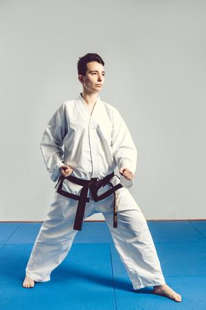 techniek: Meisje in karate pak kimono in studio op grijze achtergrond. Vrouwelijk kind toont judo of karate stans in witte uniform met zwarte riem. Individuele krijgskunst sport. Volledig lichaamsportret