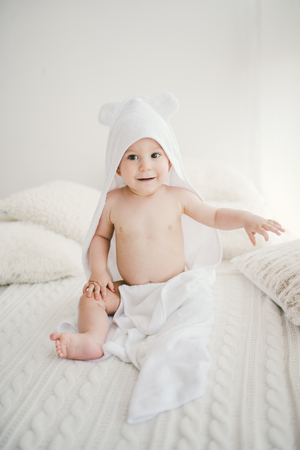 beautiful smiling newborn baby boy covered with white bamboo towel with fun ears. Sitting on a white knit, wool plaid bright interior. The natural light from the window