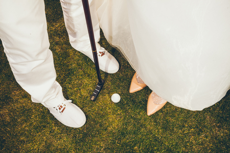 loving couple in wedding clothes playing Golf. Legs on green grass
