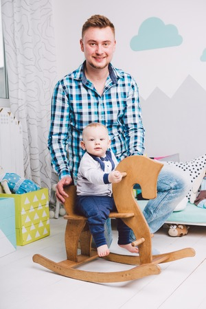 dad and son. A child is playing on a wooden horse in the apartment. Bright interior Stock Photo
