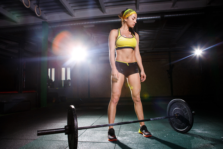 A beautiful young girl in the gym trains the muscles of the legs and back, deaet exercises deadlift, sits with weight, holds a bar in her hands Stock Photo
