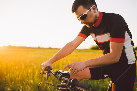 A young brunette guy on a mountain bike uses a cycling computer, a navigator in the field at sunset of the day