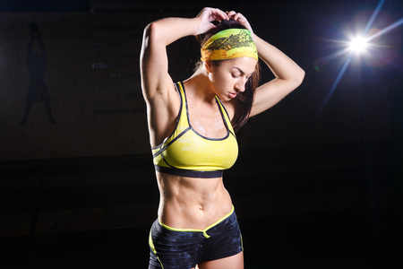 beautiful, strong, slender, in good physical shape in the gym doing exercises. Dressed in short shorts and tank top green, on the head bandage. Sports theme