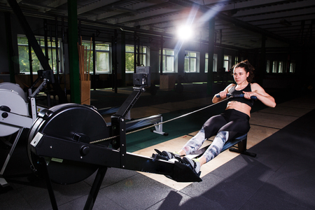 Young strong girl doing an exercise on a rowing machine. For training cardio, arms, back. Sporting concepts