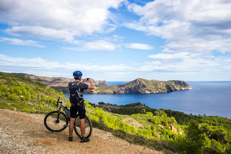 a young guy on a mountain bike trails in Spain and takes a photo on a white phone in the background of the Mediterranean sea of the rocky coast of the Costa Brava. In a blue helmet on his head and a black backpack. Sunny weather on a mountain road near the city of Cadaques