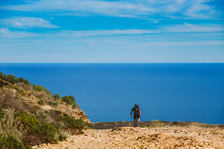 a young guy riding a mountain bike on a bicycle route in Spain on a dirt road against the background of the Mediterranean Sea. Dressed in a helmet, a dark one and a black backpack Stock Photo