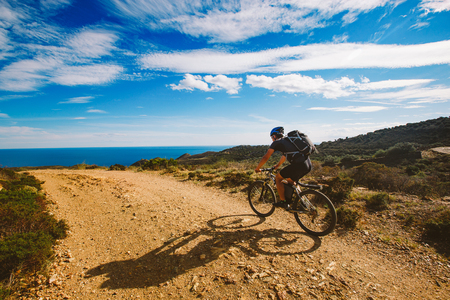 road bike: a young guy riding a mountain bike on a bicycle route in Spain on a dirt road against the background of the Mediterranean Sea. Dressed in a helmet, a dark one and a black backpack Stock Photo