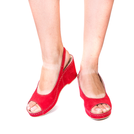 legs of a girl in summer orthopedic shoes on white isolated background