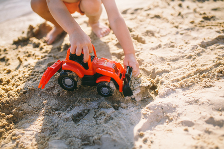 child boy playing on the beach near the river toy red tractor at sunset Stock Photo