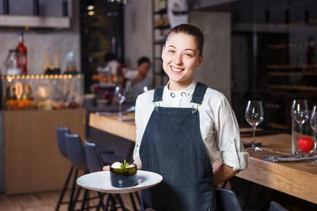 아름 다운 미소 어린 소녀 그녀의 손에 웨이터 보유 웨이터 달콤한 디저트 요리 이탈리아 요리입니다. 레스토랑 내부 뒤에서 피 각질의 앞치마와 흰 셔 스톡 콘텐츠