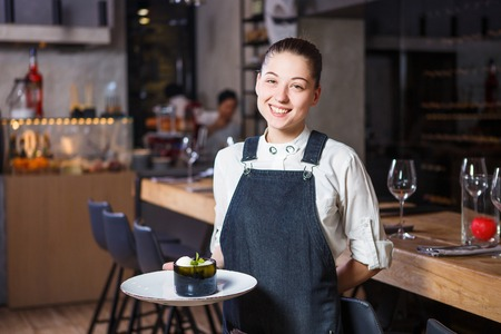 young girl with a beautiful smile a waiter holds in her hands an order sweet dessert dish of Italian cuisine. Dressed in a crusty apron and a white shirt behind the interior of the restaurant Banque d'images