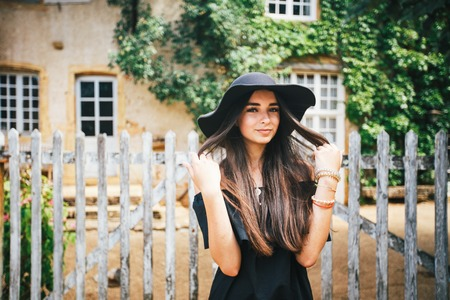 Beautiful sexy girl brunette with brown eyes in a black dress and a black hat with big brims against the backdrop of a wooden fence and an old house in a village, Burgundy in france in summer. Stock Photo