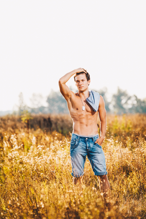 a handsome young sexy man with a strong muscular torso in an unbuttoned shirt is standing on a meadow in nature outside the city
