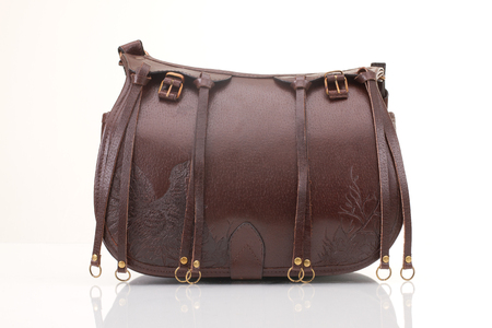 Leather hunting bag with brown ornament with patronage on white isolated background.