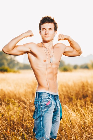 Beautiful sexy muscular man posing outdoors outside the city in the field and listening to music on headphones.