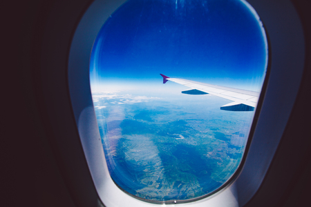 plan éloigné: Looking through window aircraft during flight in wing blue sky.