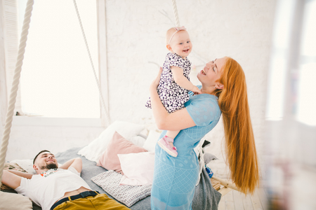 young beautiful woman with red long hair in a blue dress holds a child on her hands one year blonde near the bed on which lies a man resting.