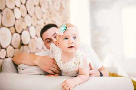 Dad and daughter child starting to walk one year inside the house in the living room laughing and joy on the couch against the wooden wall background. Stock Photo
