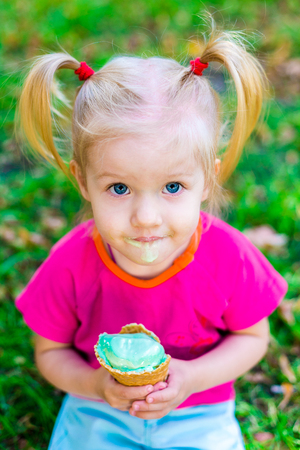 little funny Caucasian girl blonde with blue eyes with two tails on head eating an ice cream in a waffle cup of blue sitting on green grass. All face dirty in melted ice cream.Looks up at the camera Stock Photo