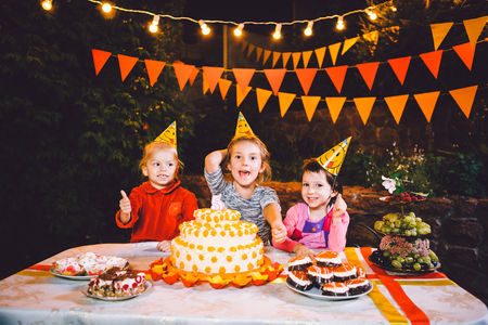 Childrens birthday party. Three cheerful children girls eating cake with their hands and smearing their face. Fun and festive mood in the decorated courtyard decor with bright bulbs and colored flags