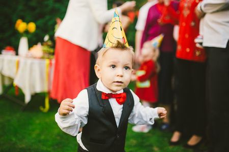 baby boy alone birthday in suit with with black vest, white shirt and red butterfly on the background of a crowd of people, guests at a holiday in the courtyard of the house.