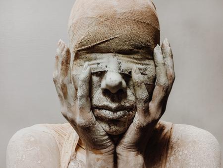 in make-up is een vrouw in verband en klei als een mummie zonder ogen op een monofone achtergrond. Halloween-thema